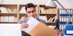 A man looking at the content of an envelope - T1 Shipping Note