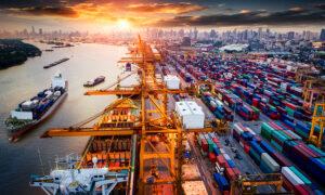 Überseehafen bei Sonnenuntergang mit Containern zum Export und Frachtschiff.